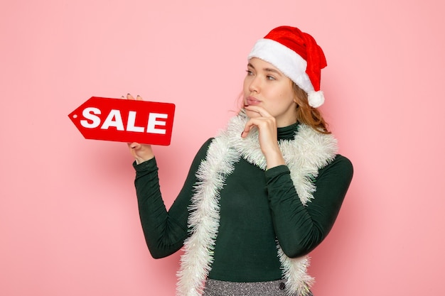 Mulher jovem segurando uma venda vermelha escrita na parede rosa, natal, feriado, ano novo, foto
