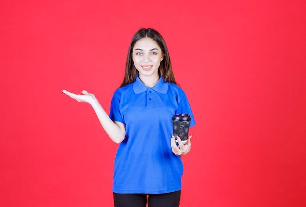 Mulher jovem segurando uma xícara de café descartável preta