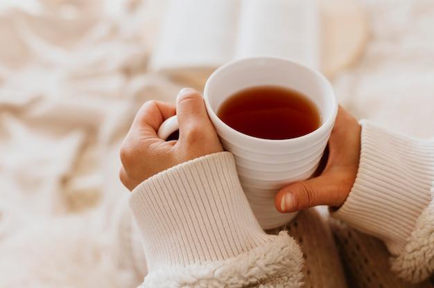 Mulher jovem segurando uma xícara de chá enquanto aproveita as férias de inverno