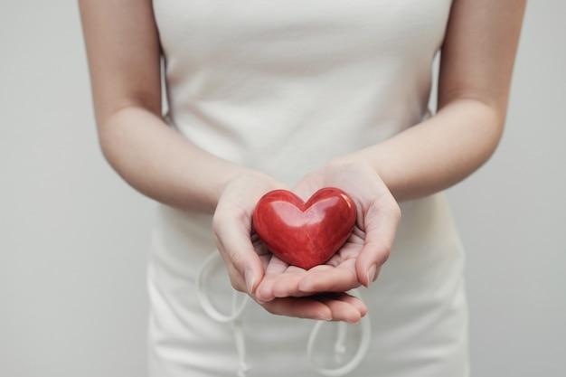 Mulher jovem, segurando, vermelho, coração, seguro saúde, doação, conceito