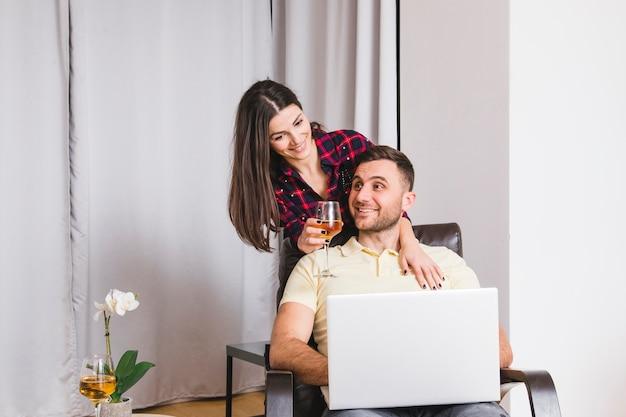 Mulher jovem, segurando, wineglass, estar, atrás de, a, homem, usando computador portátil