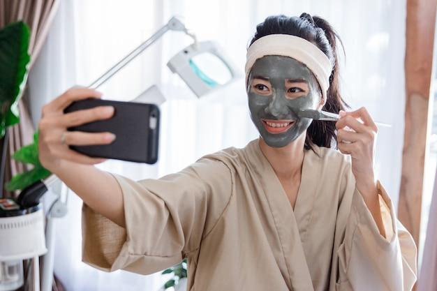 Mulher jovem selfie ao usar lama de máscara facial