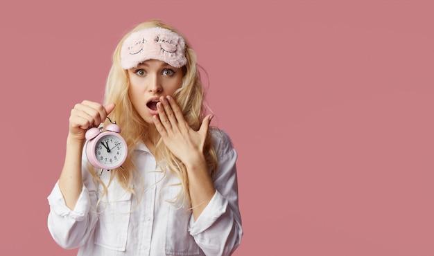 Mulher jovem sem sono de pijama e máscaras de dormir em uma parede rosa. despertador acordou a mulher