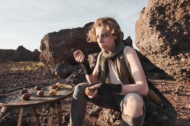 Mulher jovem sem-teto sentada na pedra comendo batatas ao ar livre