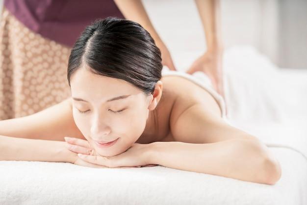 Mulher jovem sendo massageada em um salão de beleza com um ambiente claro