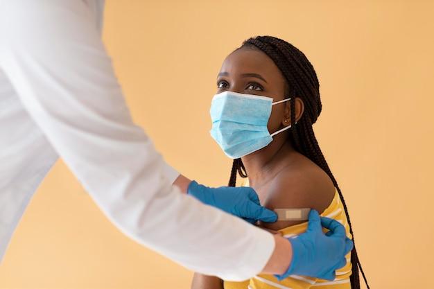 Mulher jovem sendo vacinada de perto