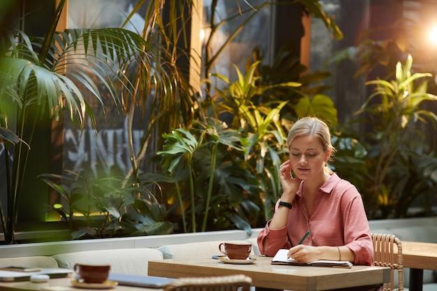 Mulher jovem sentada à mesa e fazendo anotações em um bloco de notas enquanto bebe café na cafeteria