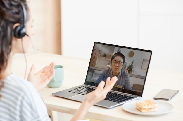 Mulher jovem sentada à mesa na cozinha, discutindo algo com seu colega por meio de videochamada