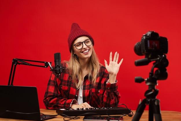 Mulher jovem sentada à mesa trabalhando como dj de rádio ela sorrindo e acenando para a câmera no estúdio