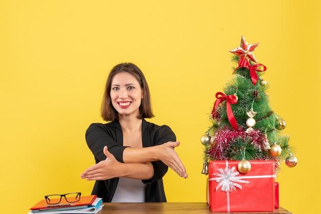 Mulher jovem sentada a uma mesa e pedindo a alguém para se sentar perto da árvore de natal decorada no escritório em amarelo