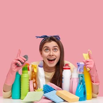 Mulher jovem sentada ao lado de produtos de limpeza
