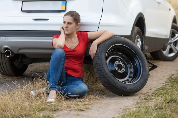 Mulher jovem sentada ao lado de um carro com um pneu furado e esperando por ajuda