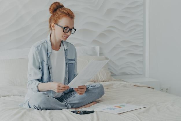Mulher jovem sentada com as pernas cruzadas em uma cama confortável verifica documentos financeiros e calcula o orçamento familiar