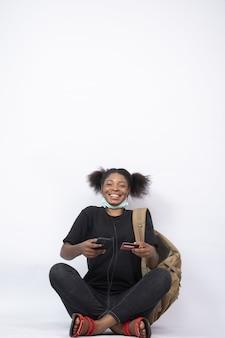 Mulher jovem sentada com as pernas cruzadas usando o celular e o cartão de crédito, sentindo-se feliz