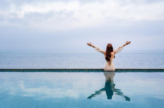 Mulher jovem sentada com os braços erguidos na beira da piscina e olhando para o mar