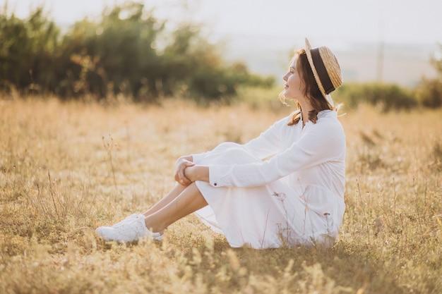 Mulher jovem sentada com vestido branco e chapéu no chão