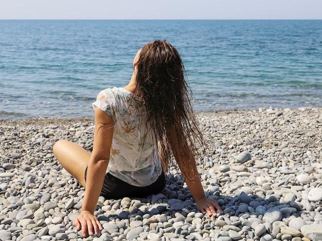 Mulher jovem sentada de costas na praia de seixos e sacudindo o cabelo molhado