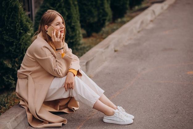 Mulher jovem sentada e falando ao telefone