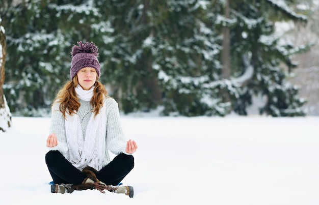 Mulher jovem sentada e meditando no parque no inverno