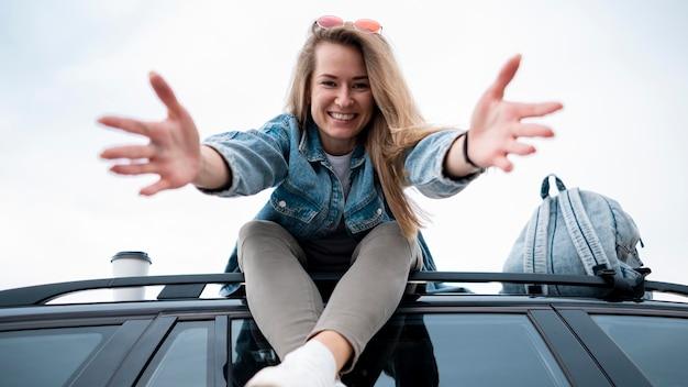 Mulher jovem sentada em cima do carro