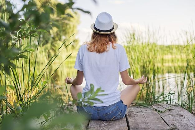 Mulher jovem sentada em posição de lótus na ponte perto da água, meditação, harmonia com a natureza, vista traseira