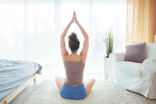 Mulher jovem sentada em seu quarto meditando