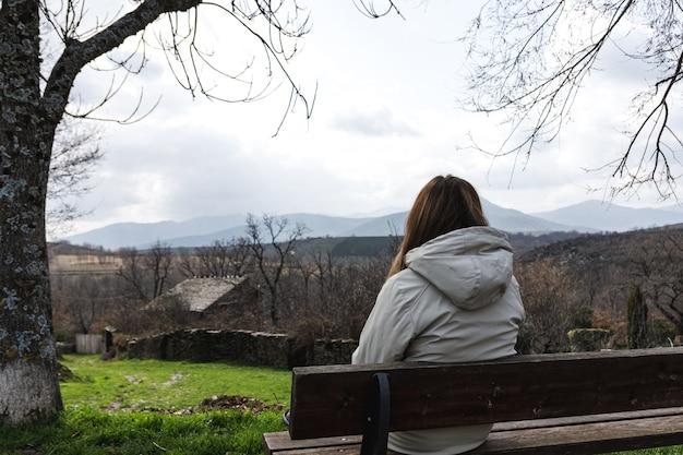 Mulher jovem sentada em um banco contemplando a paisagem