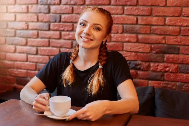 Mulher jovem sentada em um café contra uma parede de tijolos
