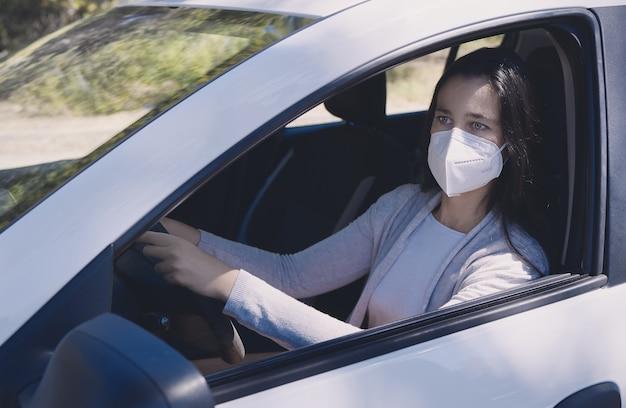 Mulher jovem sentada em um carro usando uma máscara protetora durante a pandemia de covid-19