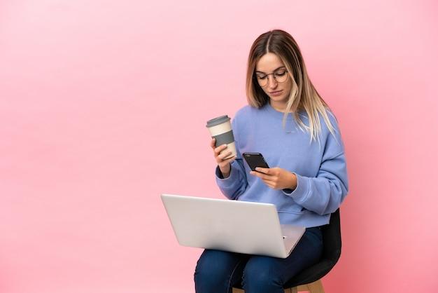 Mulher jovem sentada em uma cadeira com um laptop sobre um fundo rosa isolado segurando um café para levar e um celular