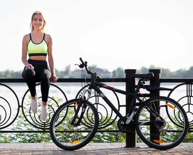 Mulher jovem sentada em uma cerca ao lado de sua bicicleta