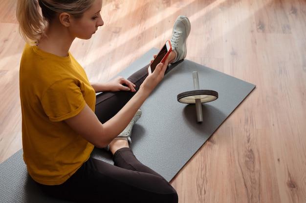 Mulher jovem sentada em uma esteira de exercícios no chão da sala de estar e fazendo exercícios online com um smartphone