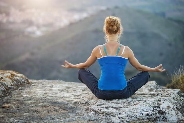 Mulher jovem sentada em uma rocha apreciando a vista do vale
