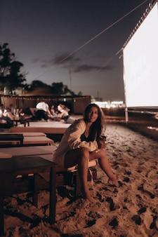 Mulher jovem sentada na cadeira à noite na praia e olhando para a câmera