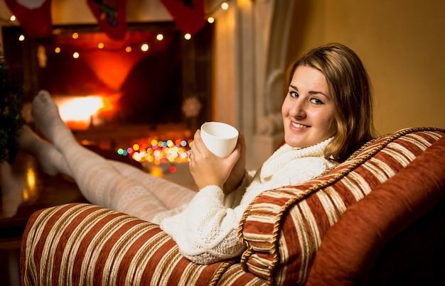 Mulher jovem sentada na cadeira ao lado da lareira e bebendo chá