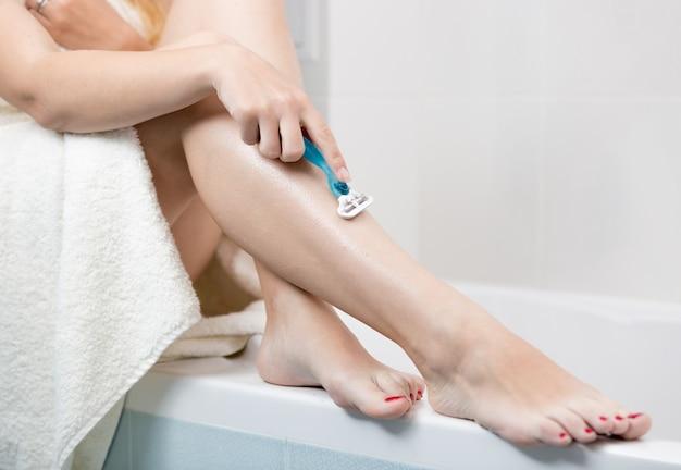 Mulher jovem sentada na casa de banho a barbear as pernas