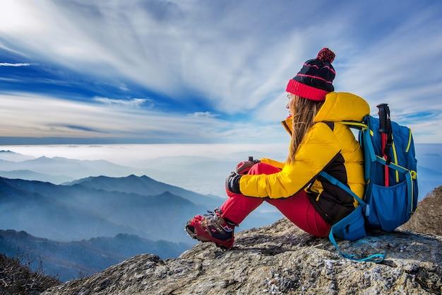 Mulher jovem sentada na colina de altas montanhas