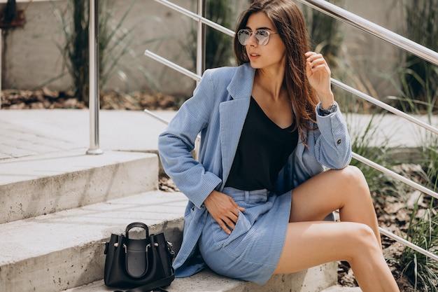 Mulher jovem sentada na escada com um terno azul