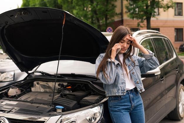 Mulher jovem sentada na frente de seu carro, tenta ligar para obter assistência com seu carro quebrado