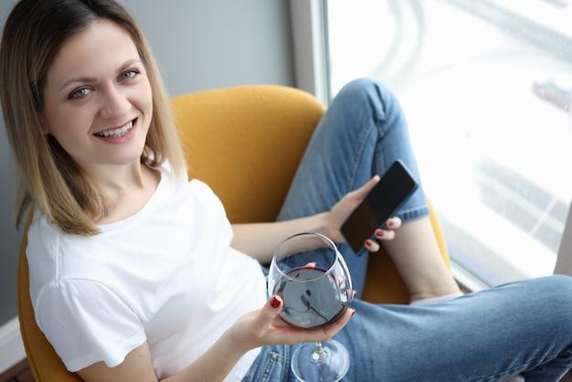 Mulher jovem sentada na poltrona com um copo de vinho tinto e telefone