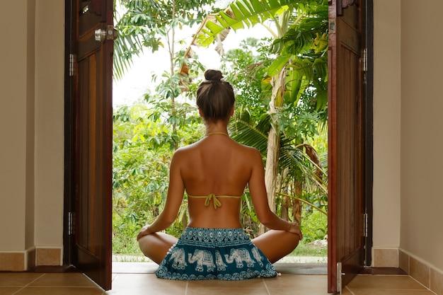 Mulher jovem sentada na porta de seu bangalô na selva