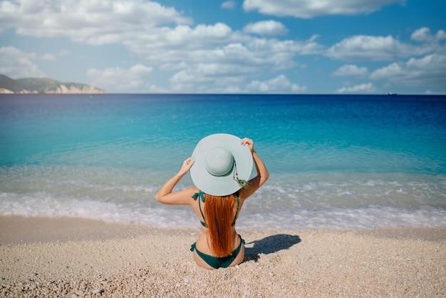 Mulher jovem sentada na praia com chapéu azul
