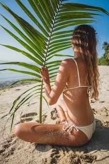 Mulher jovem sentada na praia de areia sob uma folha de palmeira