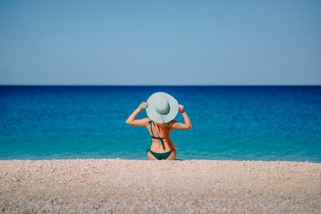 Mulher jovem sentada na praia de costas para a câmera olhando para o mar
