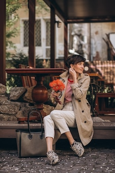 Mulher jovem sentada na rua com flores