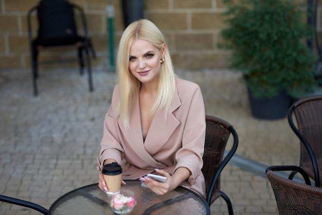 Mulher jovem sentada no café da rua tomando café e usando telefone celular