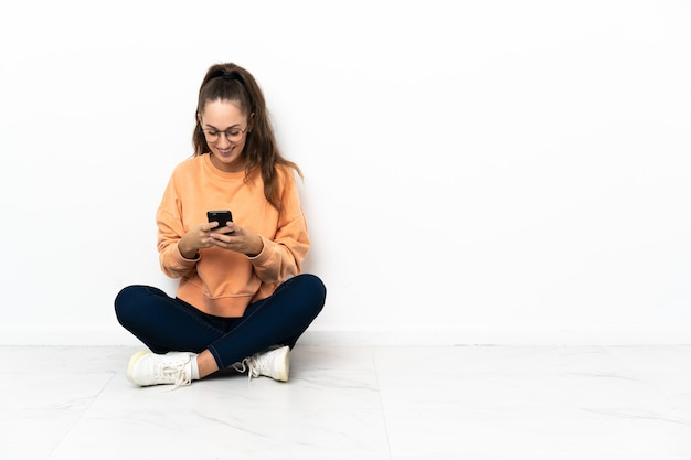 Mulher jovem sentada no chão a enviar uma mensagem com o telemóvel