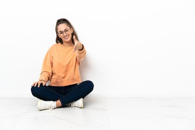 Mulher jovem sentada no chão apertando as mãos para fechar um bom negócio