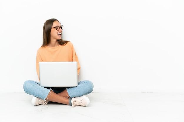 Mulher jovem sentada no chão com um laptop rindo na posição lateral