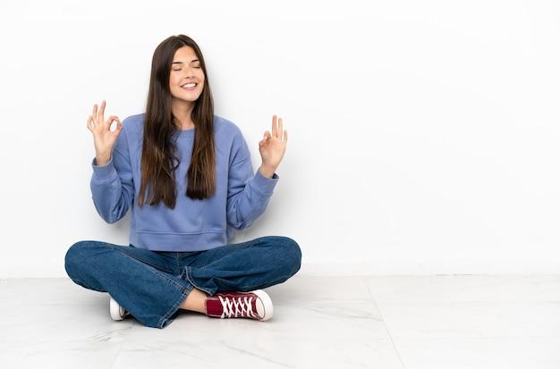 Mulher jovem sentada no chão em pose zen